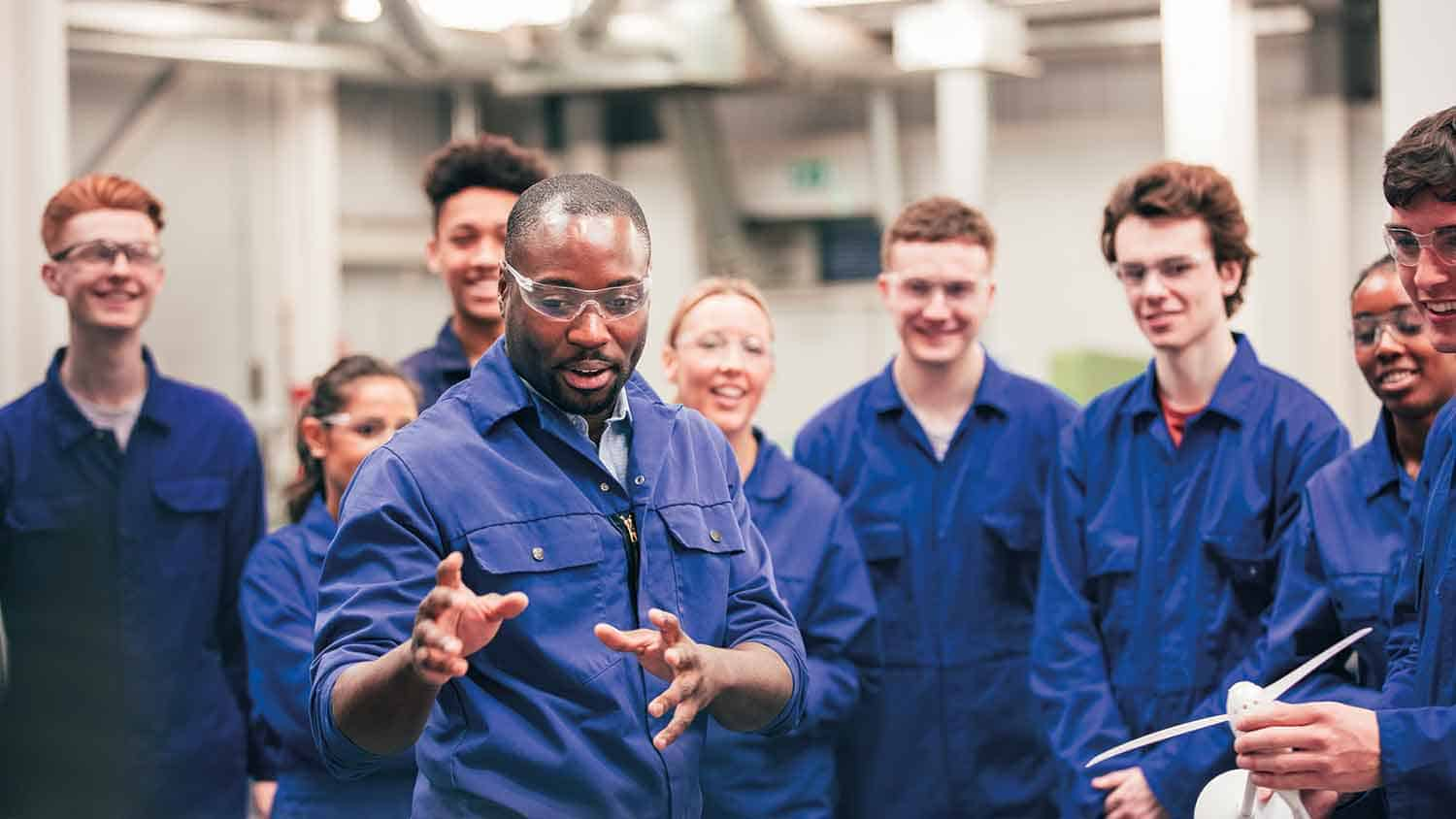 Group of apprentice mechanics listening to a teacher and smiling