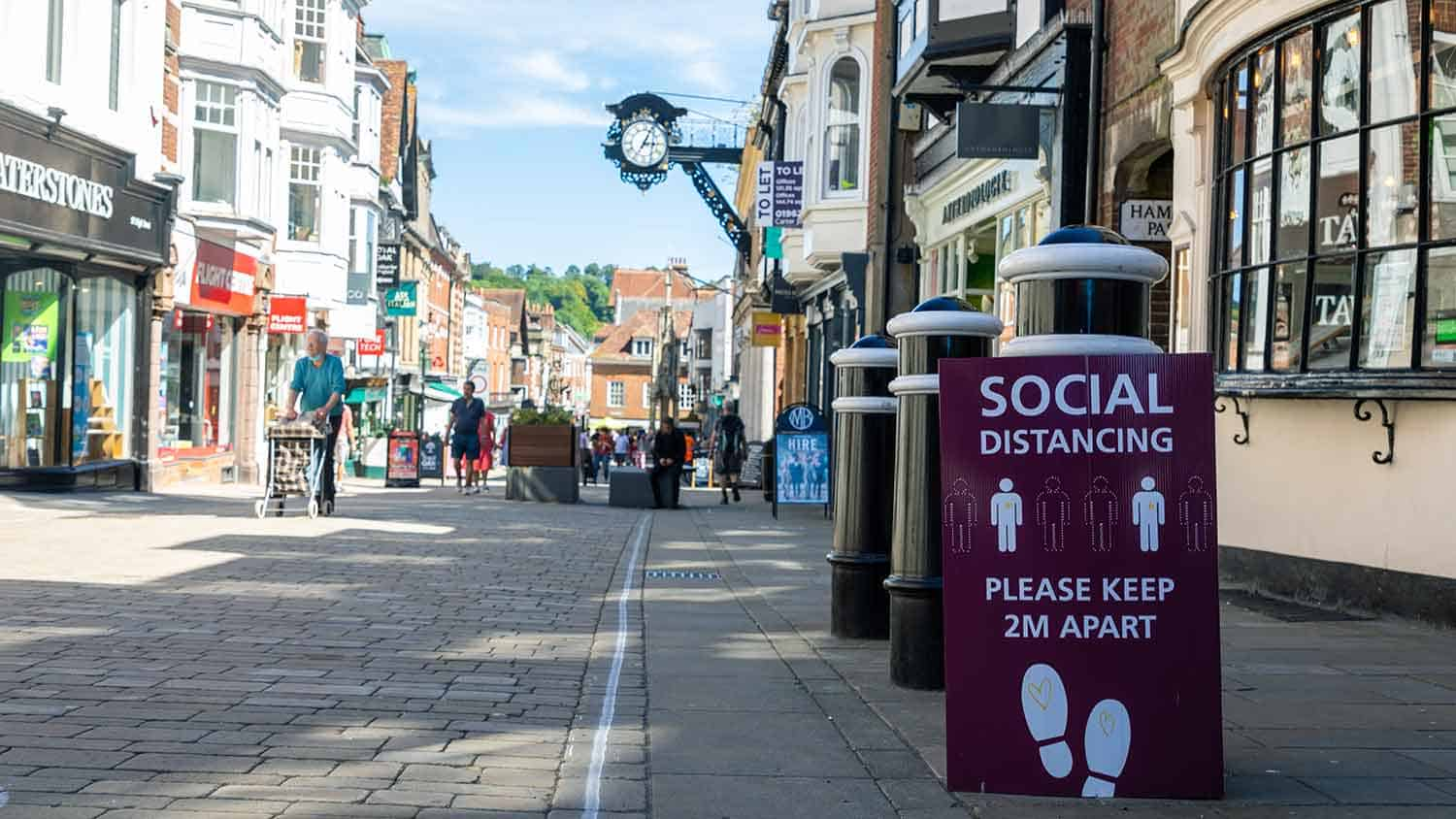 Social distancing sign in an old pedestrianised high street. Sign reads please keep 2m apart.