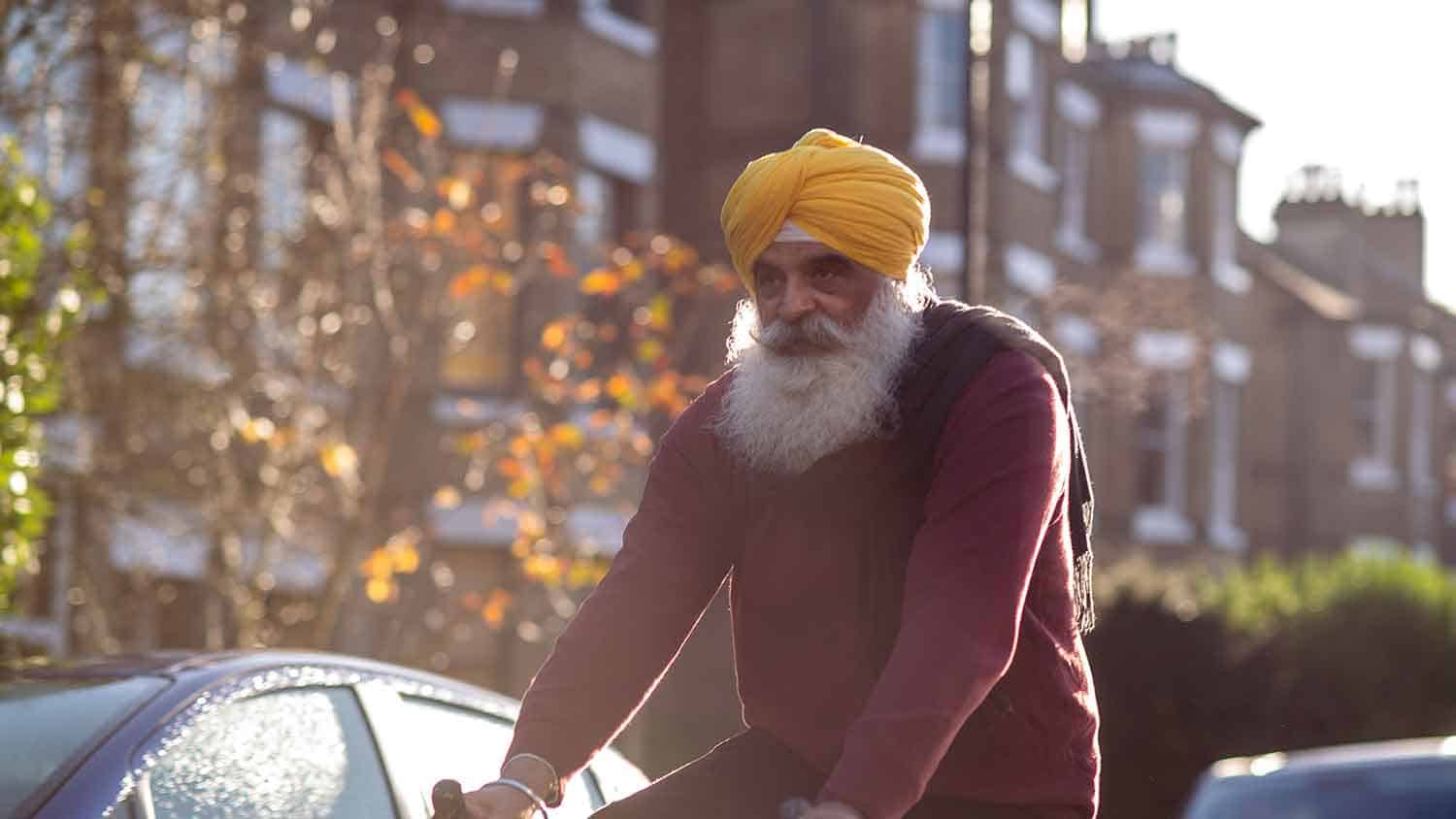 Sikh man wearing a yellow turban riding a bicycle
