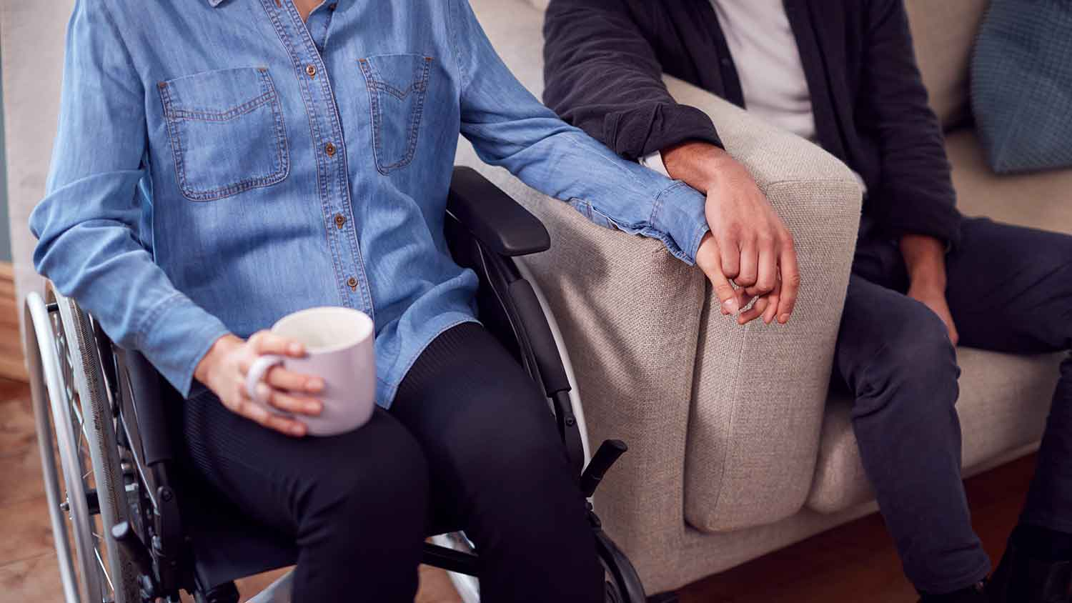 man and women holding hands sat on a chair