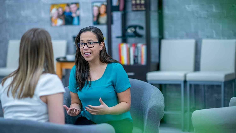 Two women talking in an office setting