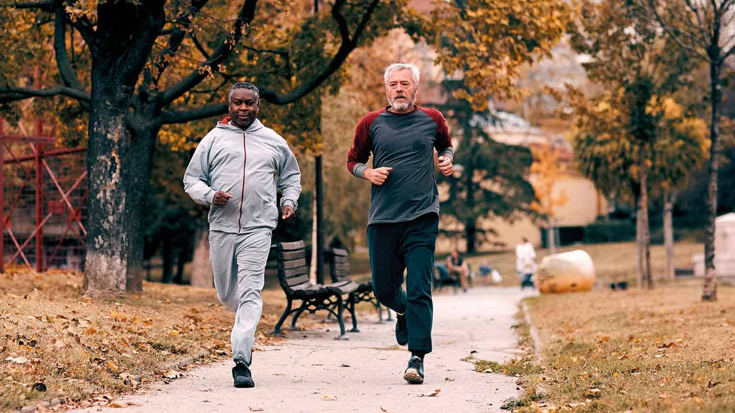 Two older men jogging through a park in early autumn