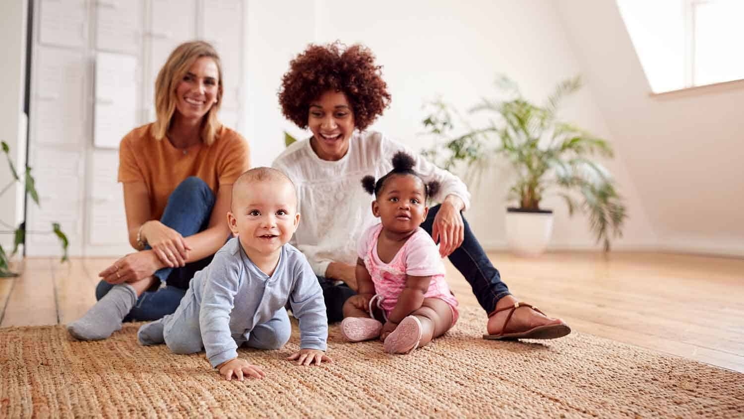Two women sat on the floor with their young babies crawling toward the camera.