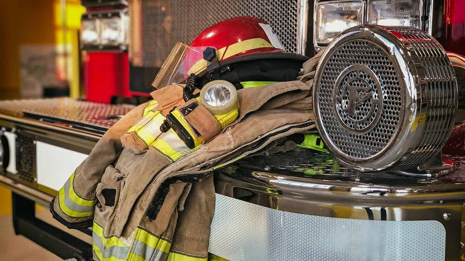 Fire mans uniform resting on the side of a fire engine, hat placed on top of jacket