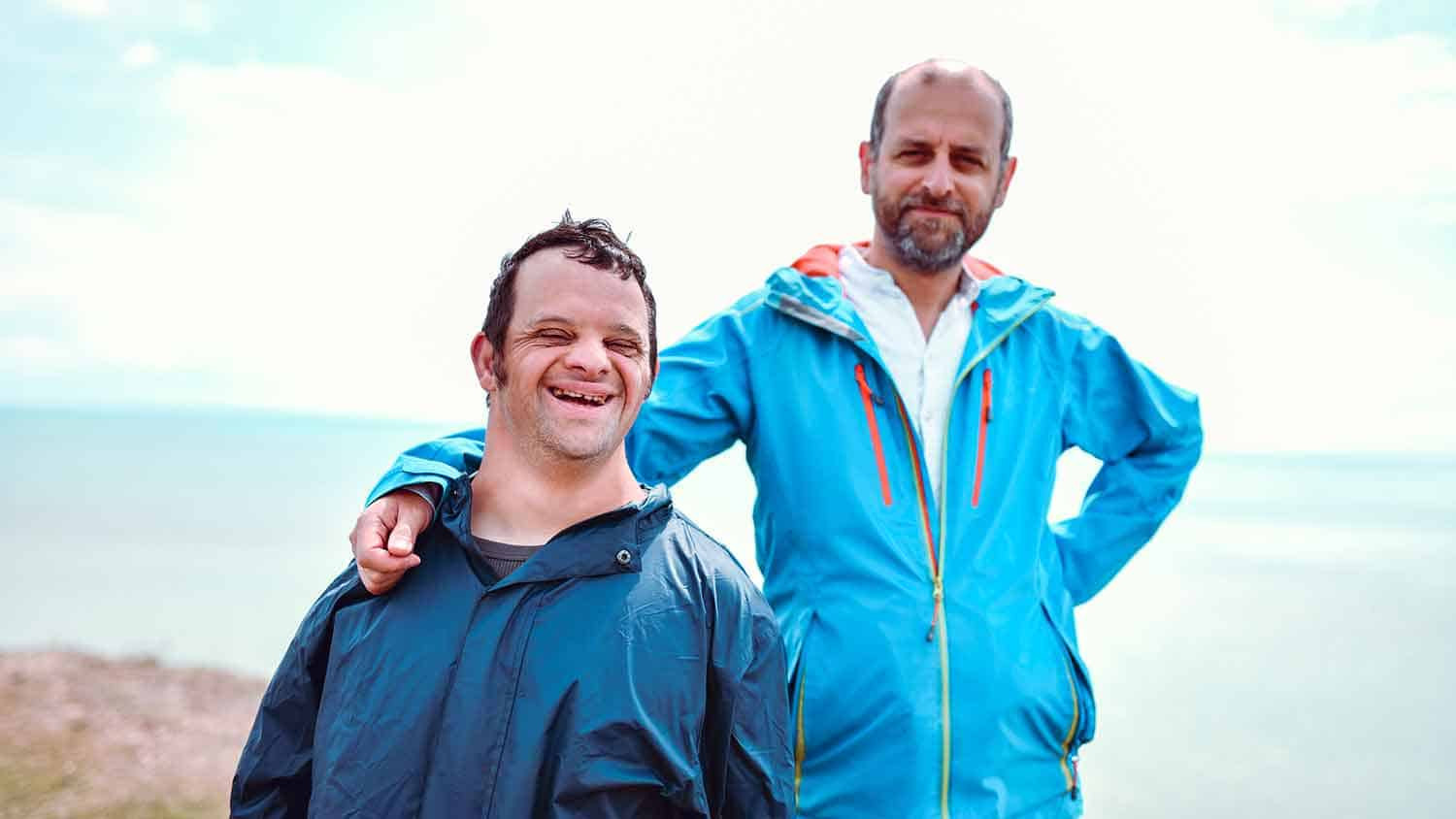 Two men looking at the camera in blue outdoor wear clothes. The man nearer the camera has down syndrome, the man behind has his hand on the other's shoulder