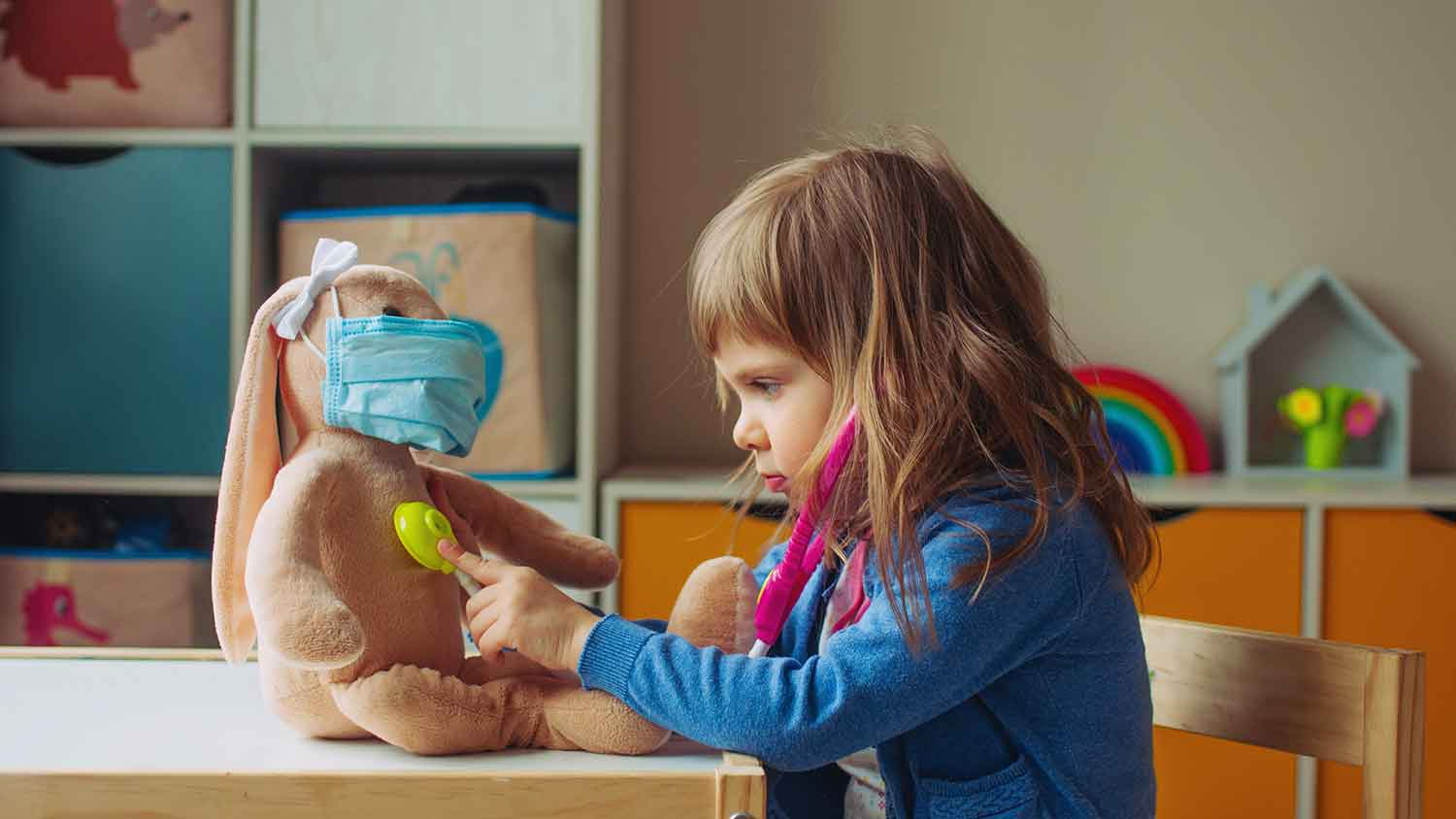 Young toddler with a toy stethascope and using it on a stuffed toy