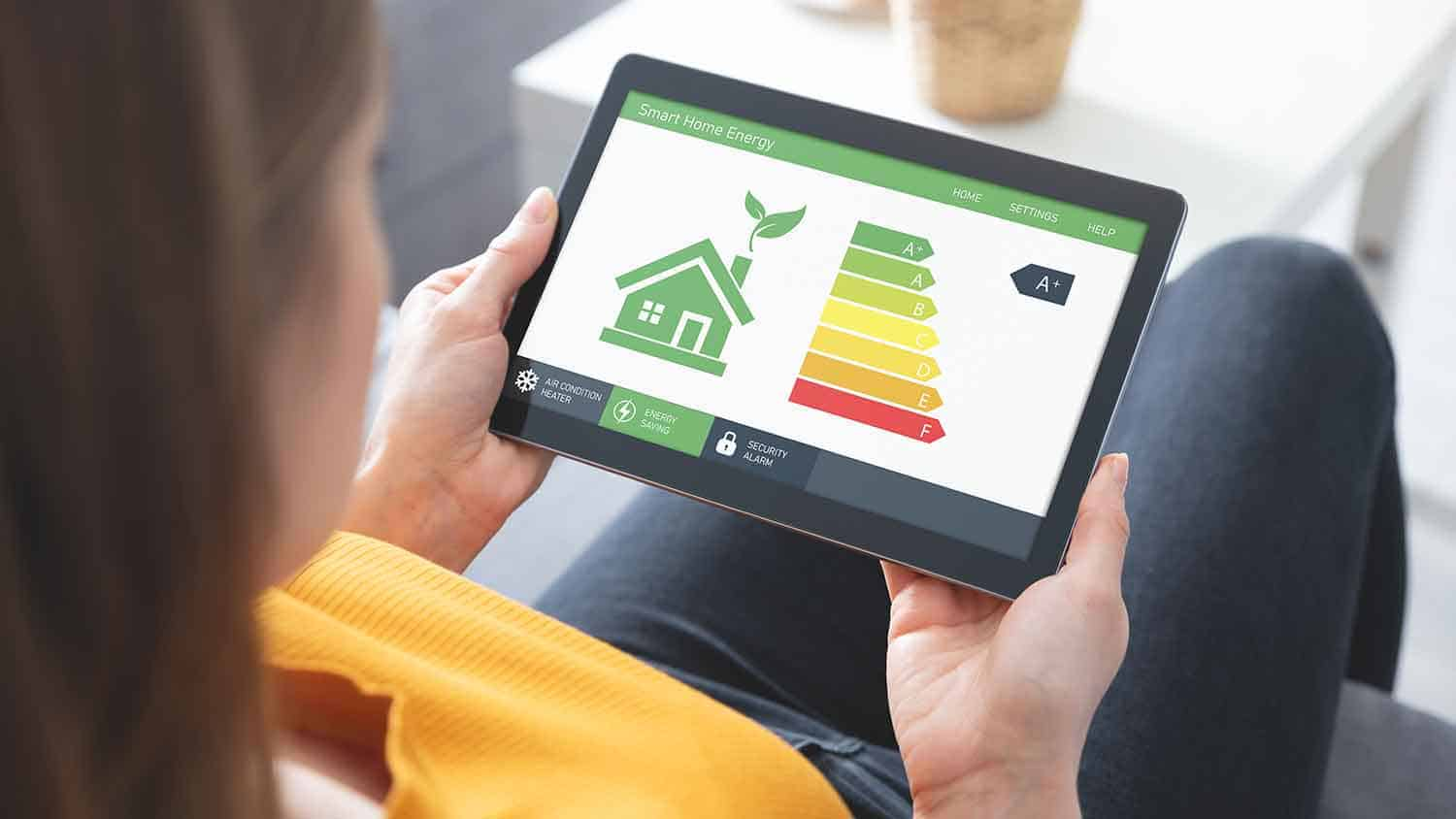 Woman looking at a computer tablet with 'smart home energy' readings on it. He rating is A+