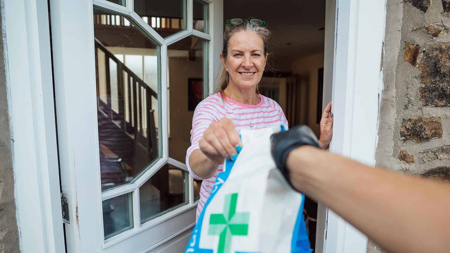 Delivery of a pharmacy prescription to a door opened by a middle aged woman grateful to receive