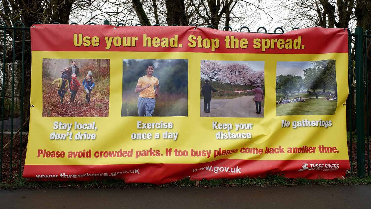 Sign saying 'use your head. Stop the spread' with examples of what you can and can't do including, 'Stay local don't drive', 'exercise once a day' 'keep your distance' and 'no gathering'.