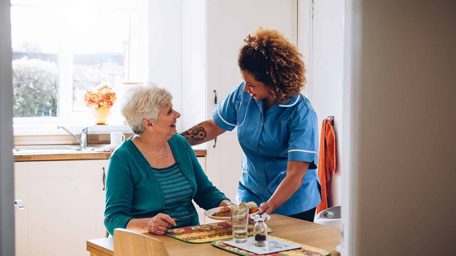 Nurse giving an older lady a meal. Both are smiling.