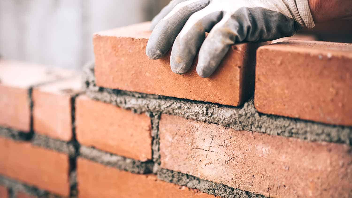 Bricklayer cementing down bricks