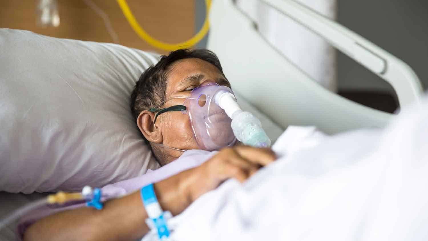 Man in hospital bed with an oxygen mask strapped over his face.