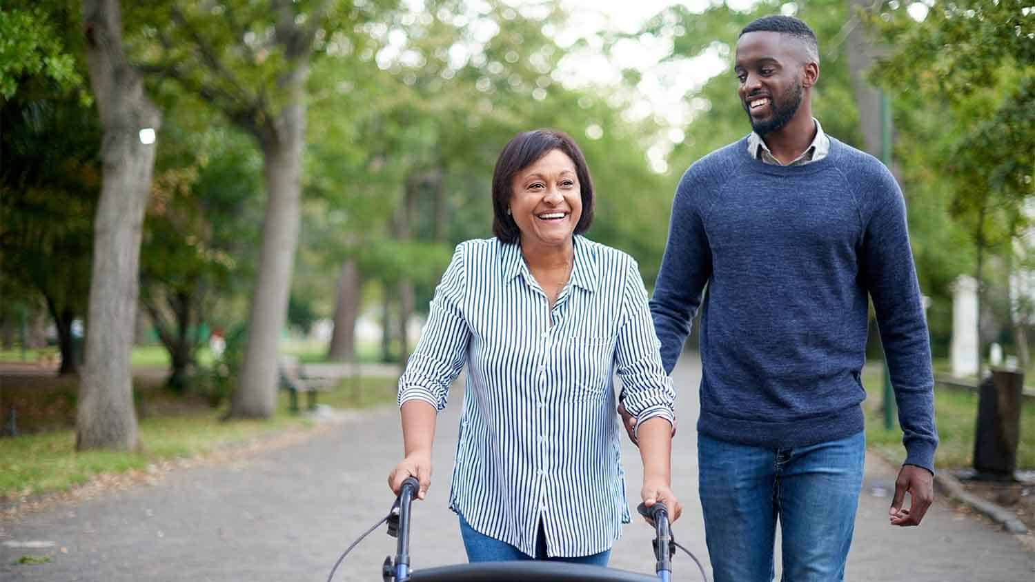 Man walking next to a woman using a walking aide