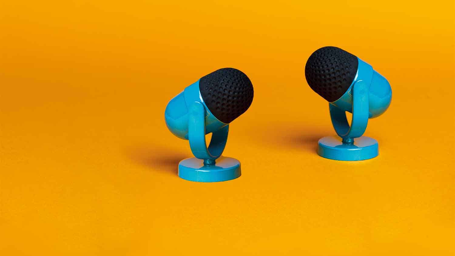 Two blue microphones on an orange background