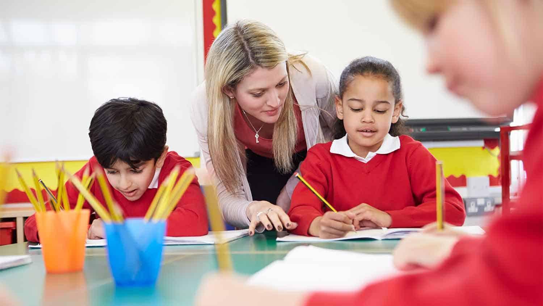 Teacher helping primary school children with their work
