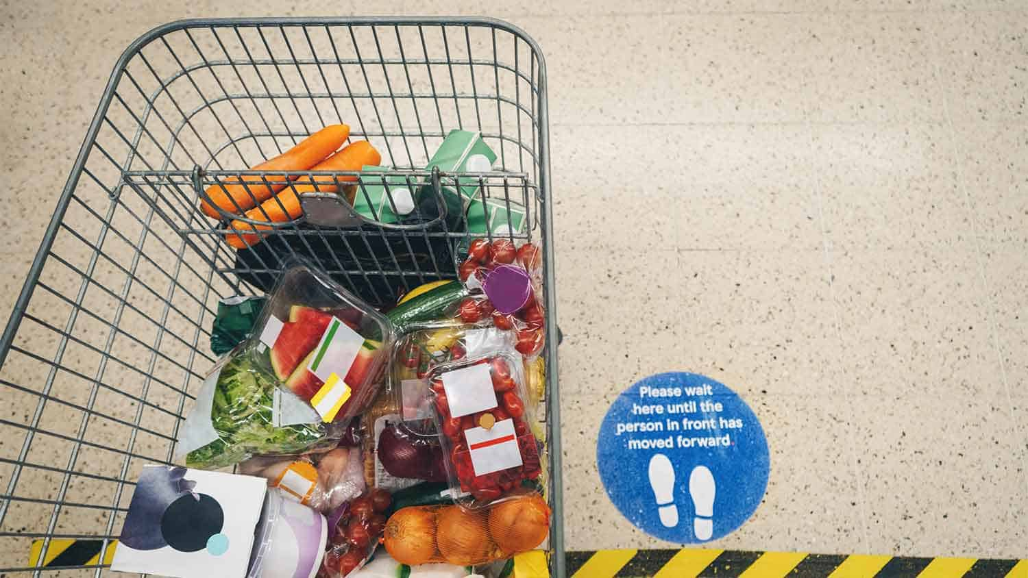 A supermarket trolley full of groceries. A covid 'keep your distance' sign is visible on the floor next to the trolley.