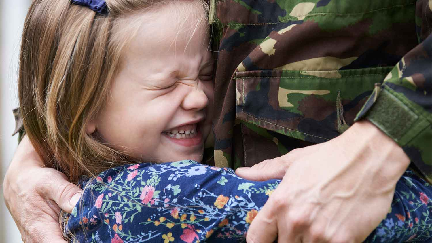Small girl hugging a man in army uniform