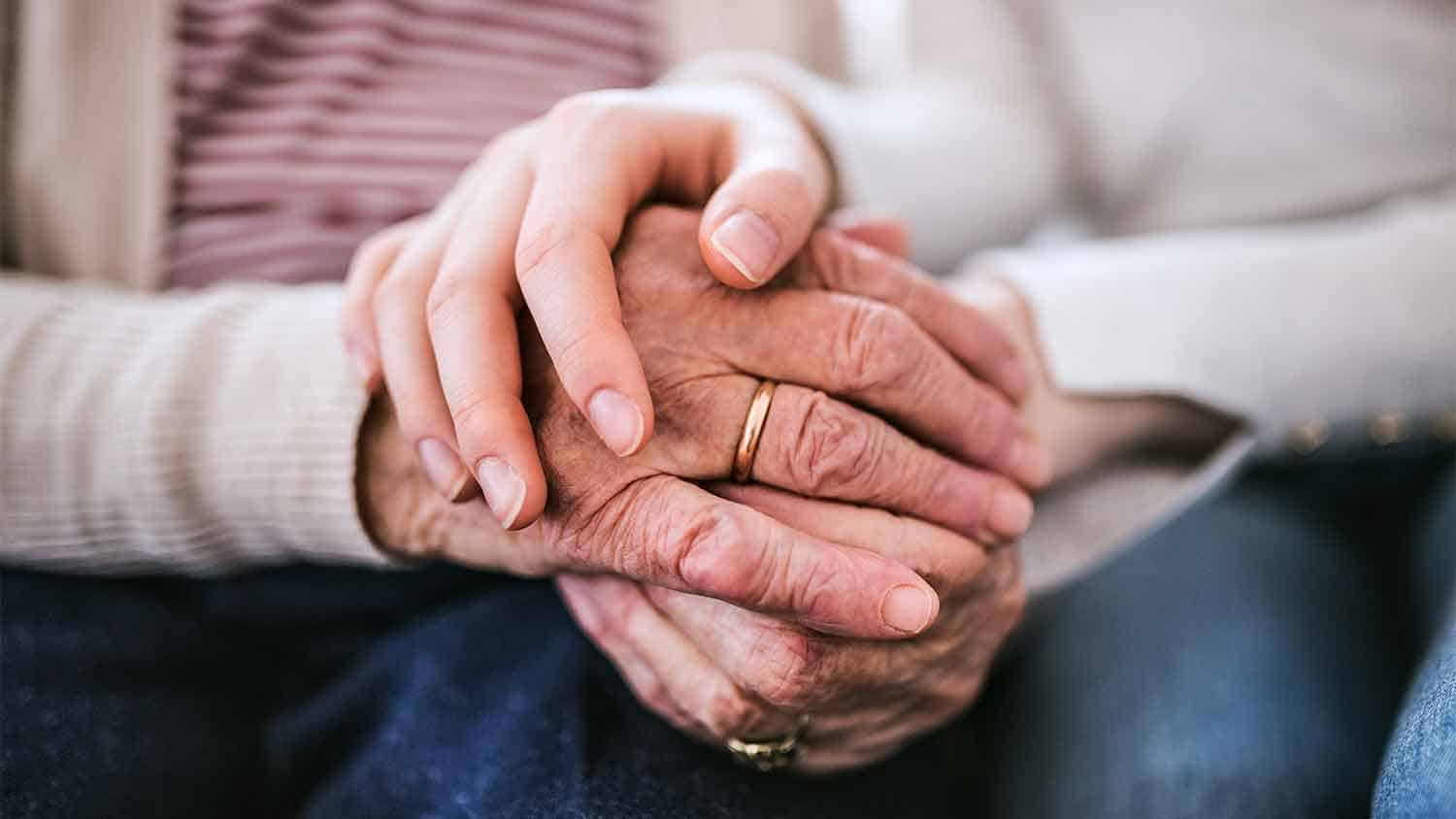 Woman and and older woman holding hands