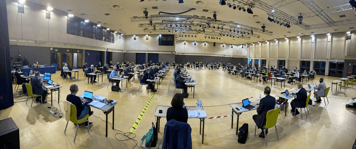 Council members sitting socially distanced in a large hall