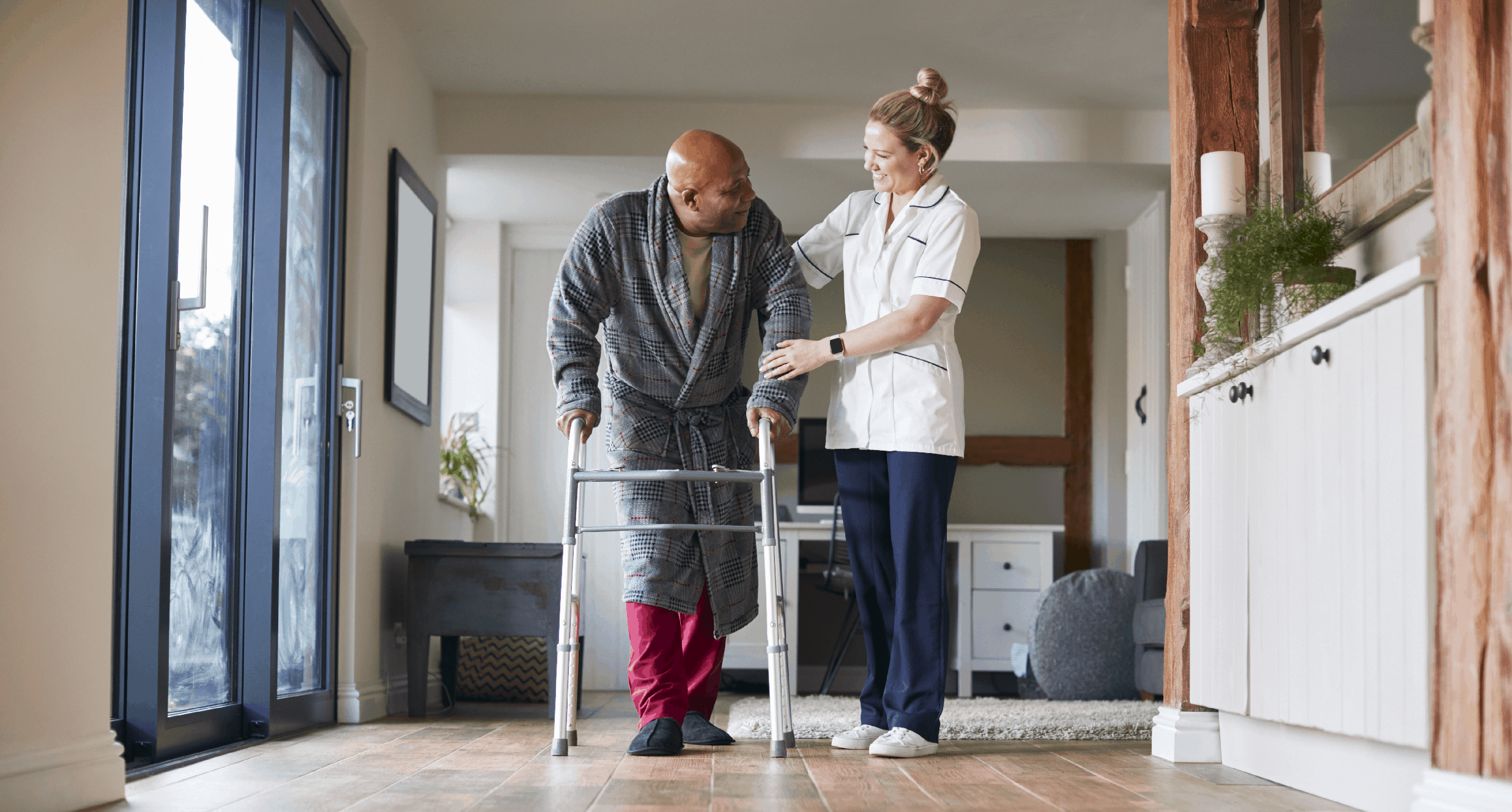 A patient being helped along the corridor by a carer