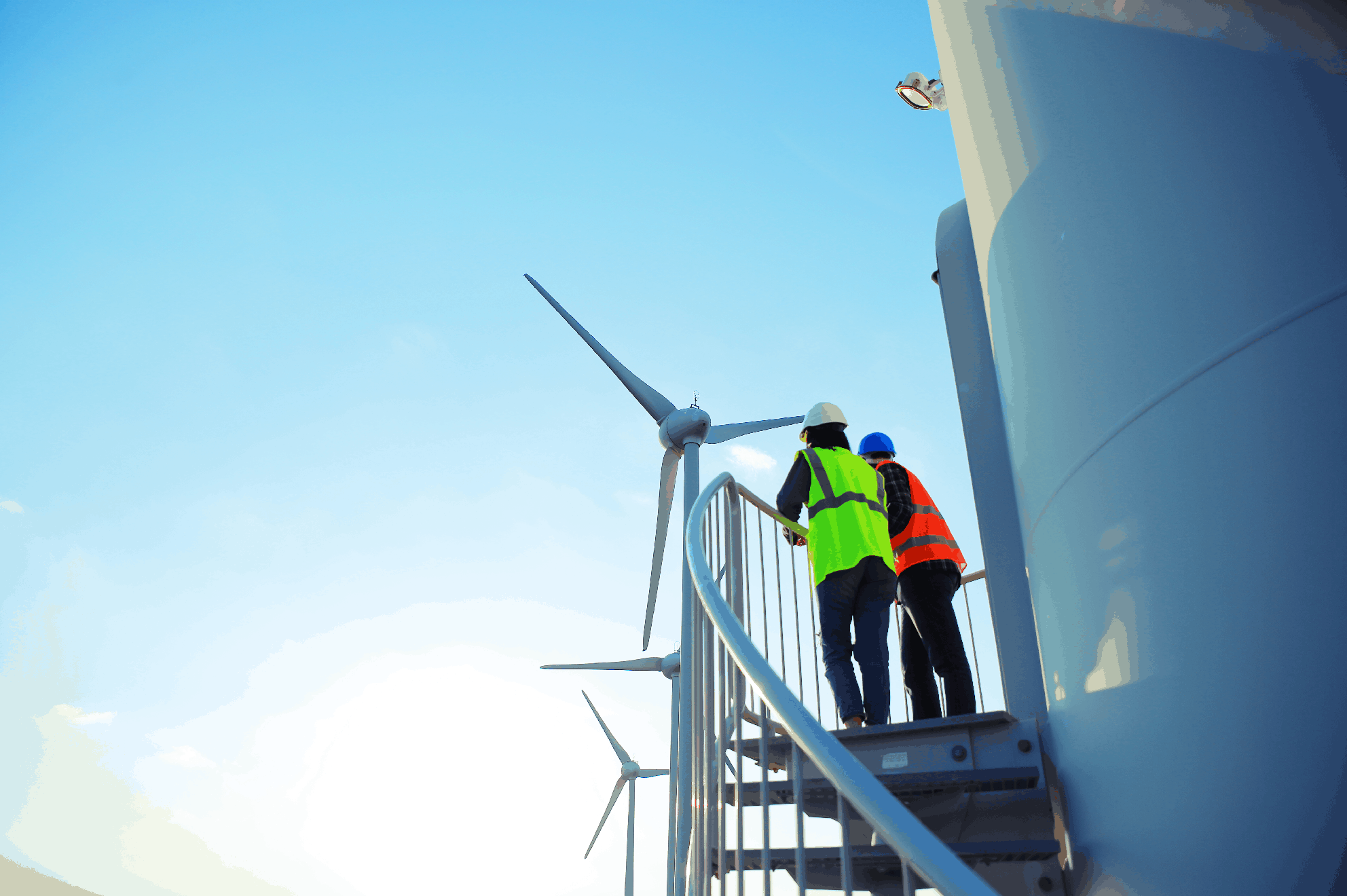 Two construction workers standing in a field of wind turbines