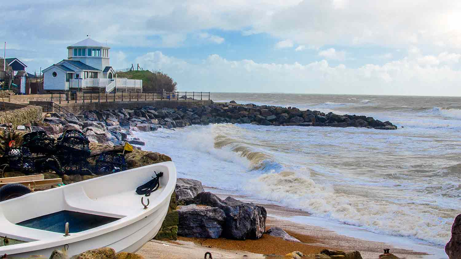 A bay with rough sea waves crashing down. A white dinghy is pointing out to sea but is safely on land