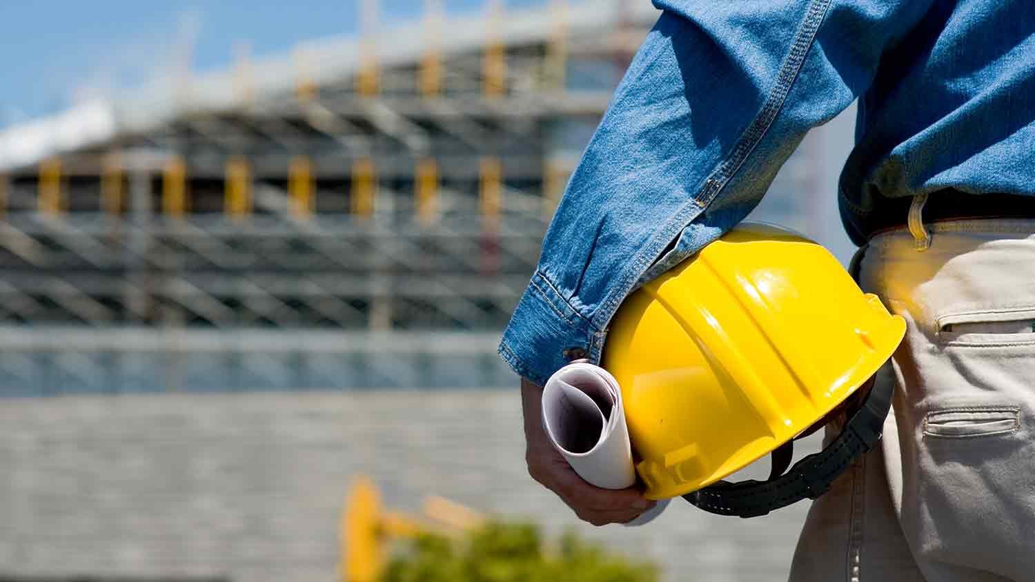 Person holdering a yellow hard hat and paper plans in front of a blurred construction site