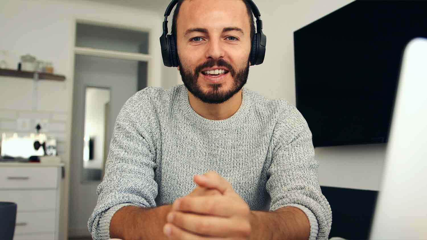 A bearded man looking at the camera whilst wearing headphones