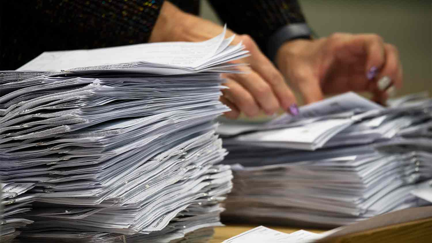 A woman flicking through a pile of papers