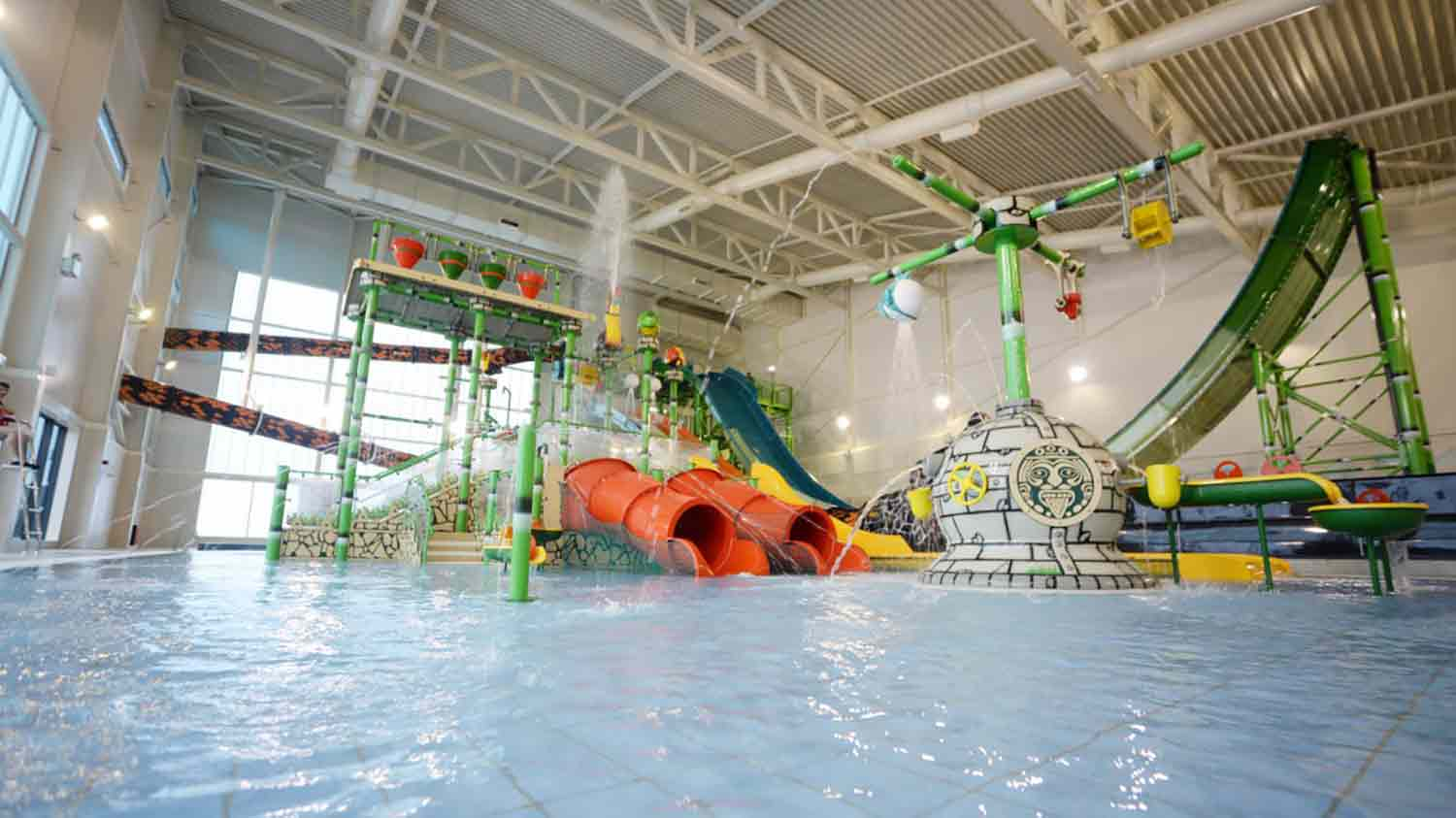 A swimming pool with a a series of water sides and fun things to do