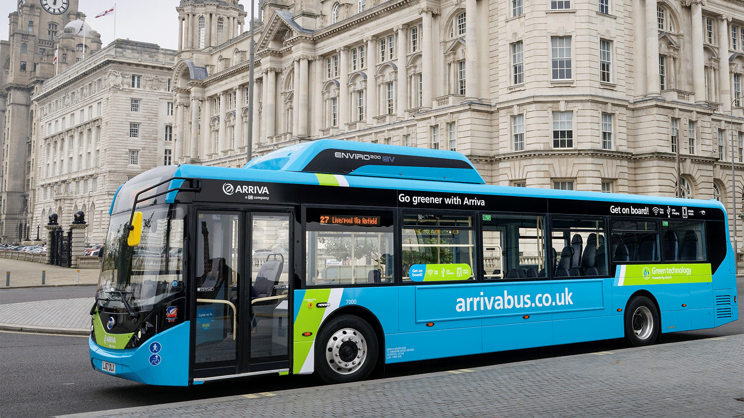 A blue bus arrives outside an old building in Liverpool