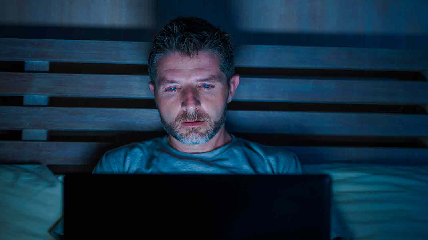 Man illuminated by a laptop in a dark bedroom. He appears upset.