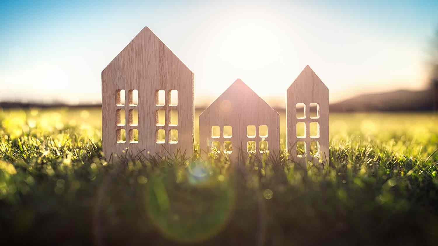 Three small parts of a wooden house lines up, the sun is shining in the background