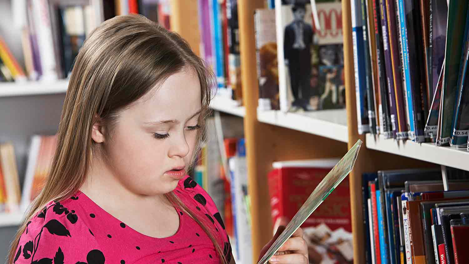 Junior school aged girl reading the back of a small thin book in a library