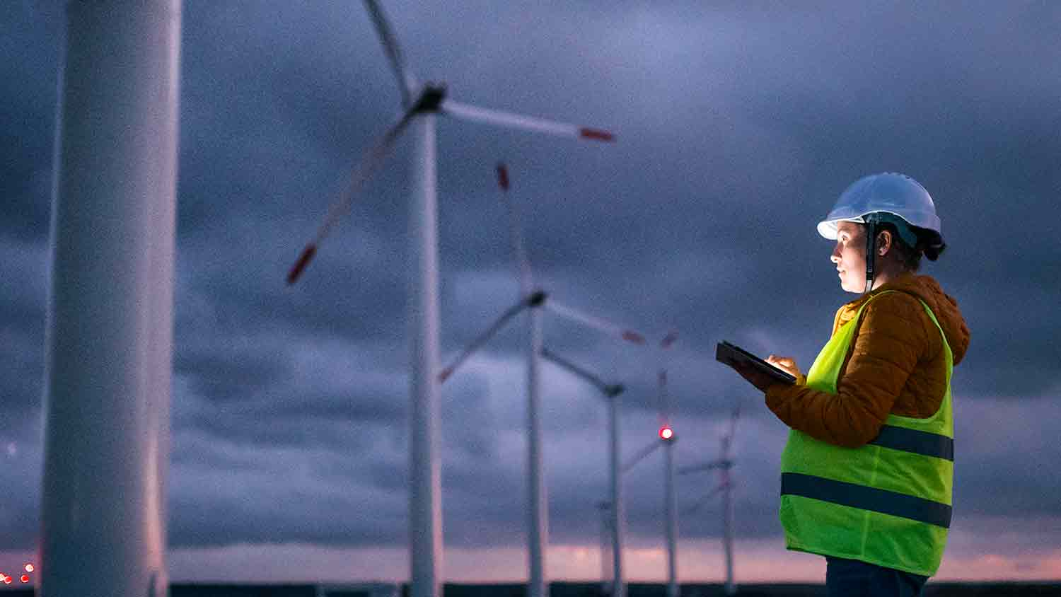 Engineer marking something on a tablet. The sky is dark and the tablet illuminates her face. The background is of wind turbines.