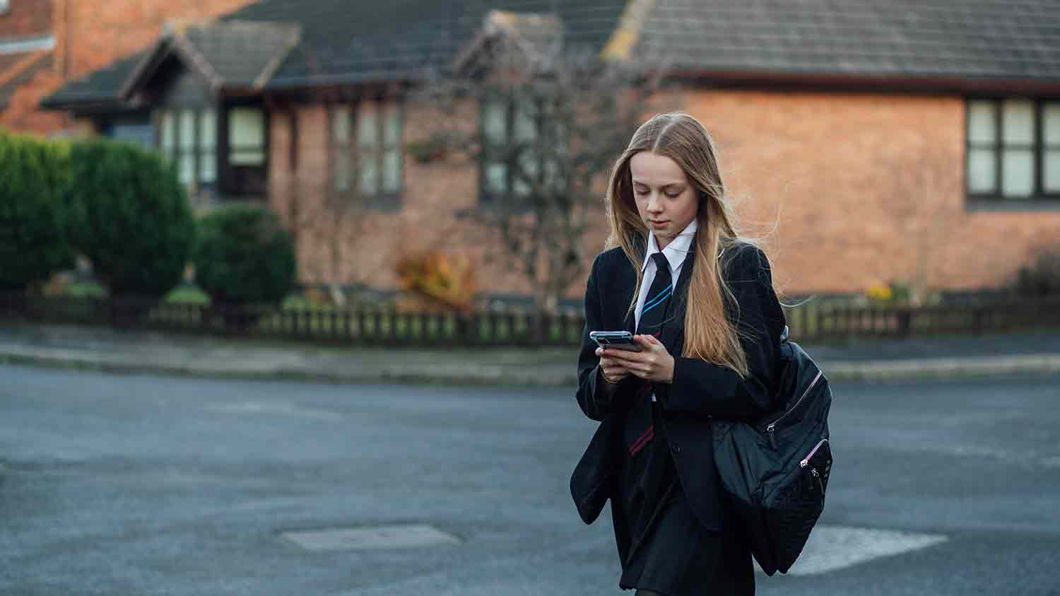 Teenage school girl walking in uniform across a road while scrolling on a mobile phone