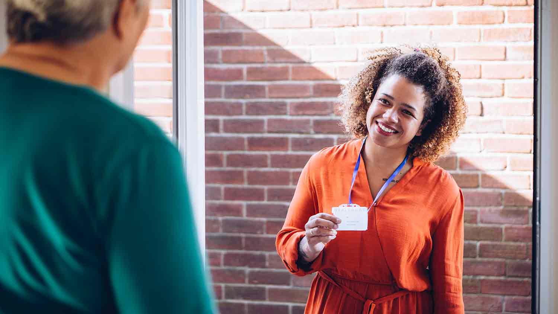 Volunteer knocking on a door and presents her identification