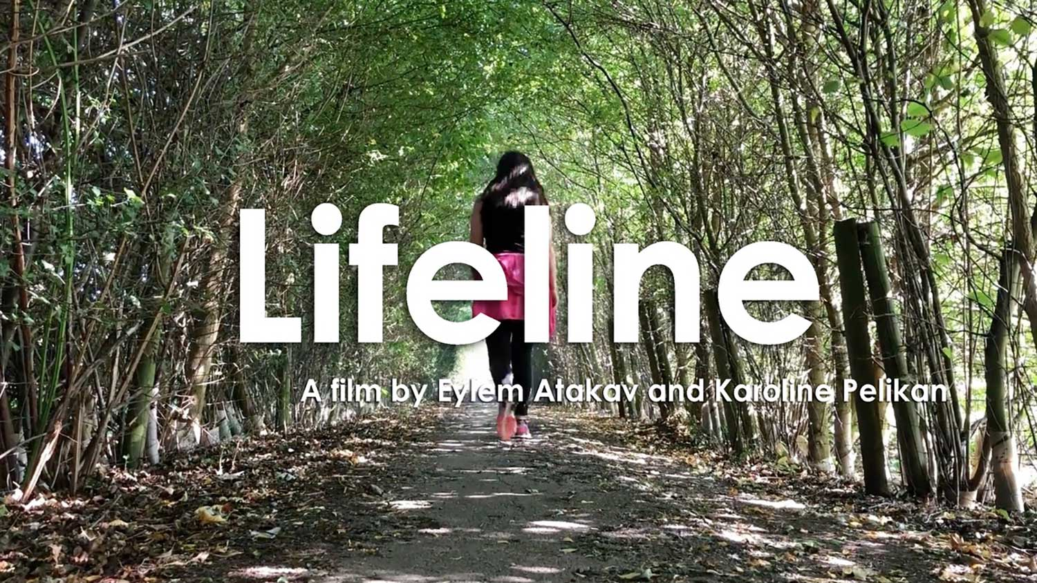 Lifeline - a film by Eylem Atakav and Karoline Pelikan. A woman in the background walks through a forest dappled with sunshine.