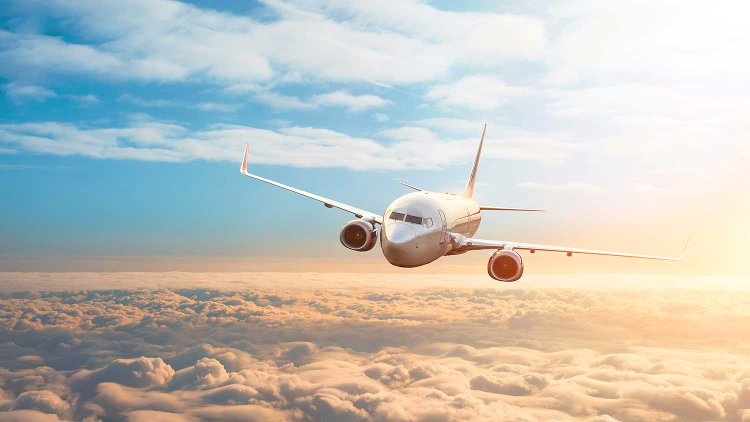 A plane glides above the clouds, the sun is bright in the background