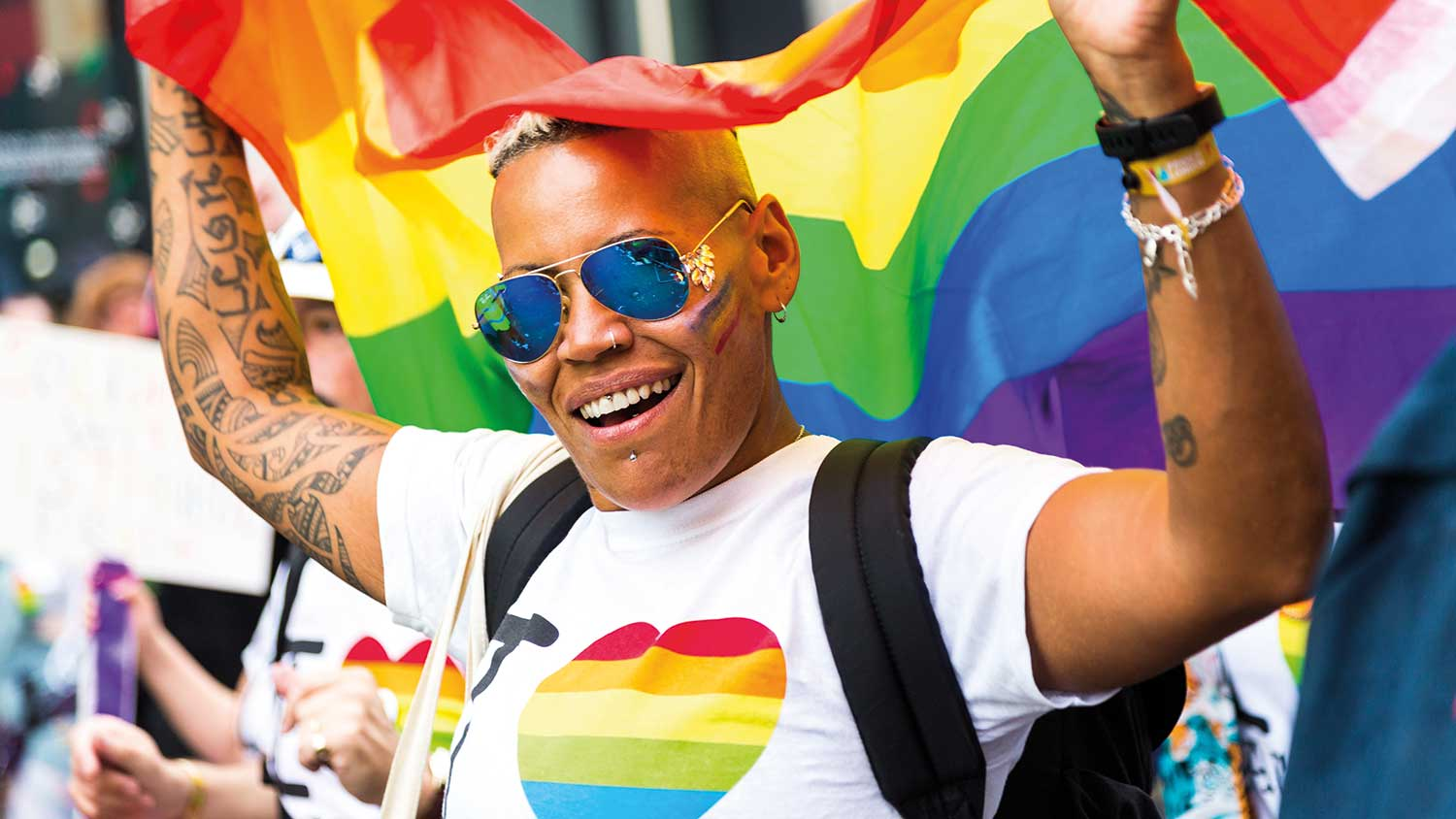A person enjoying pride, holding a rainbow flag above their head and smiling to the camera