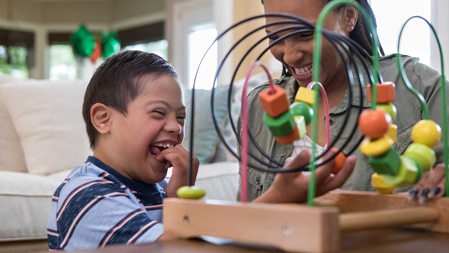 A child with down syndrome is playing with a toy, moving shapes across a wire. He and his teacher are laughing and happy.