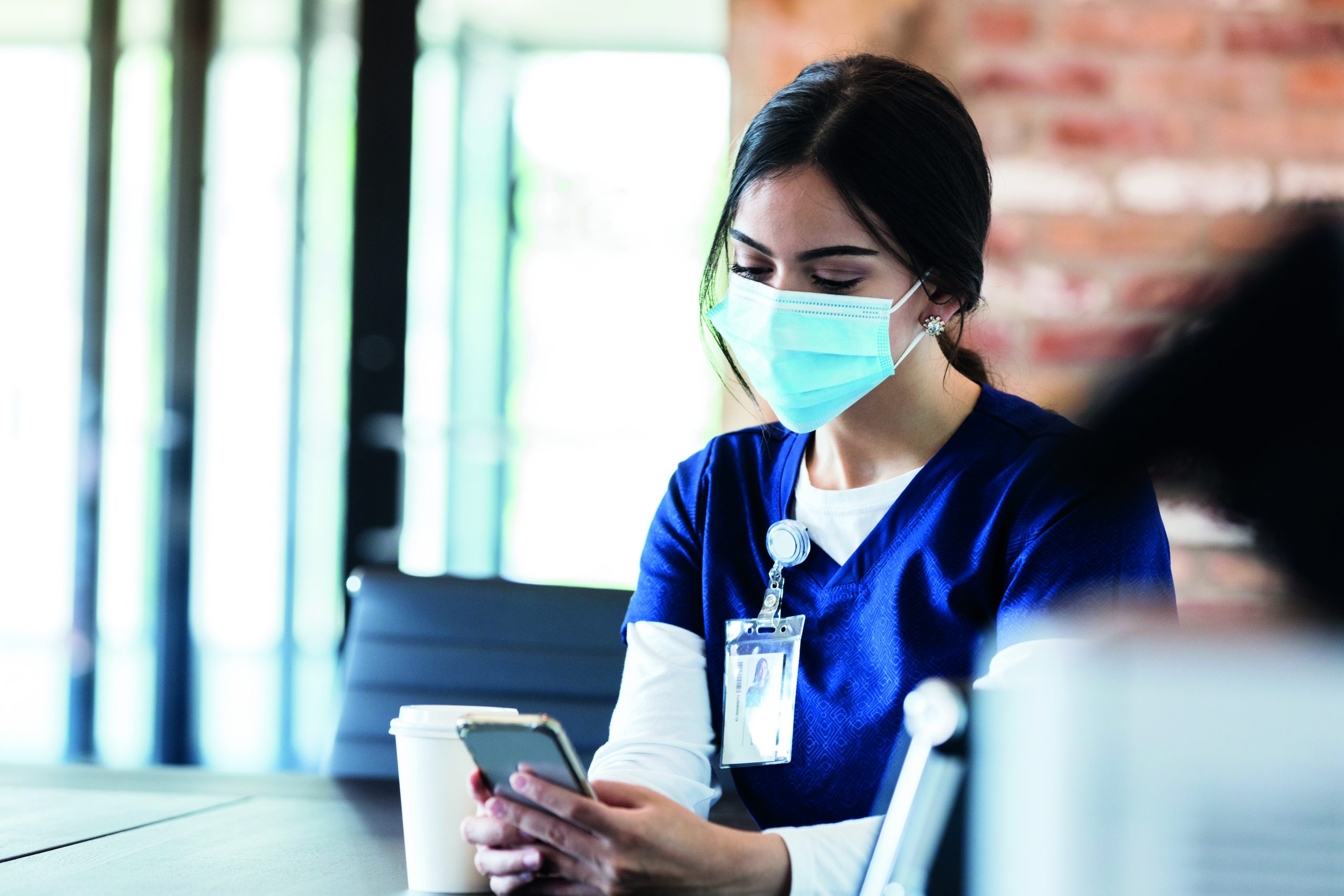A female healthcare professional wears a mask while on break from her shift. She is checking for messages on her smartphone. She is wearing a protective face mask.