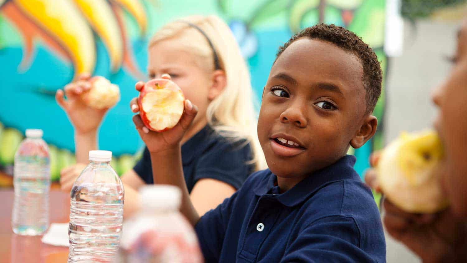 A young boy eating an apple as part of his packed lunch at school.