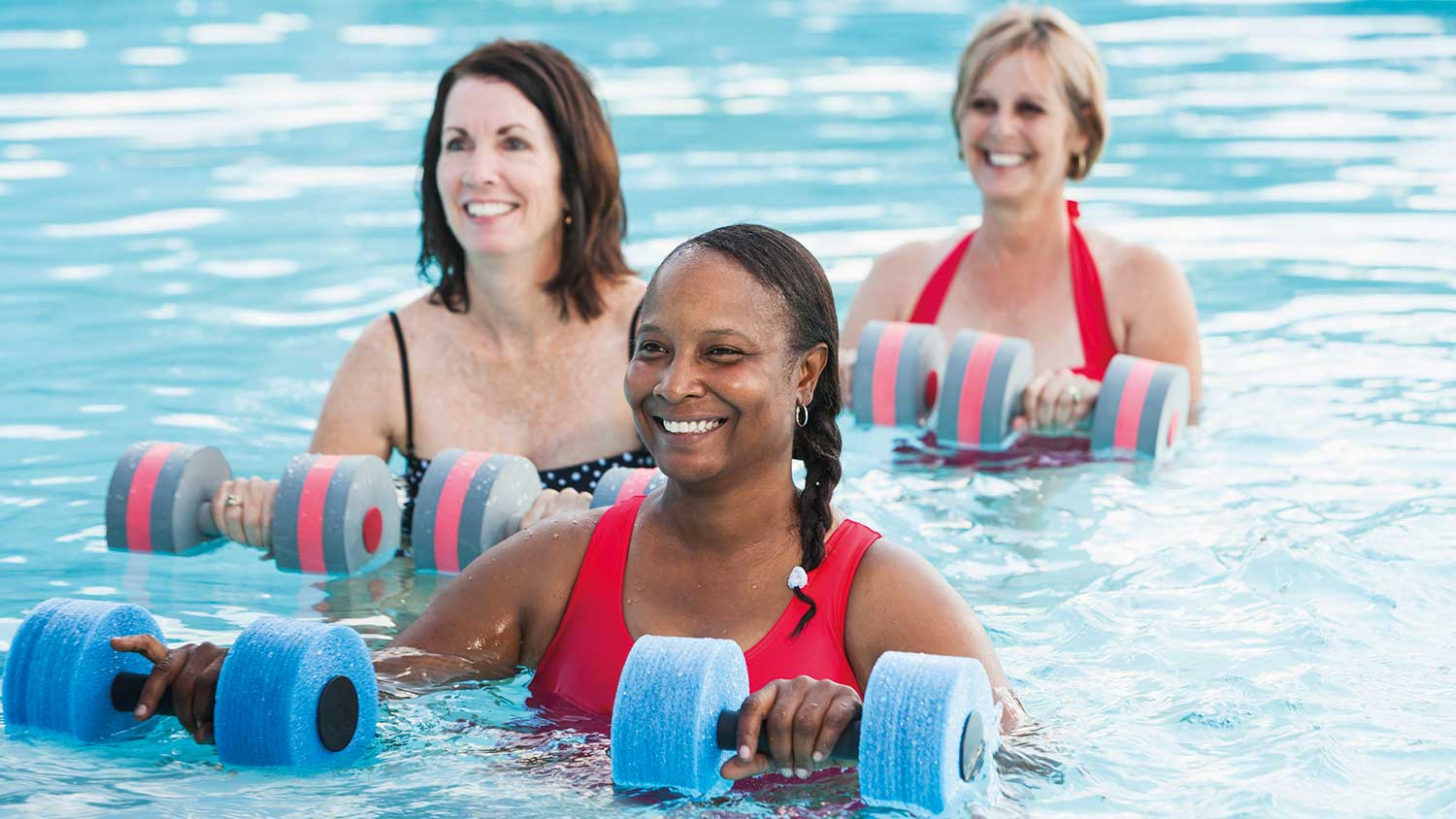 Three women looking at an instructor whilst standing in the water ready for an exercise class. They are holding water weights.