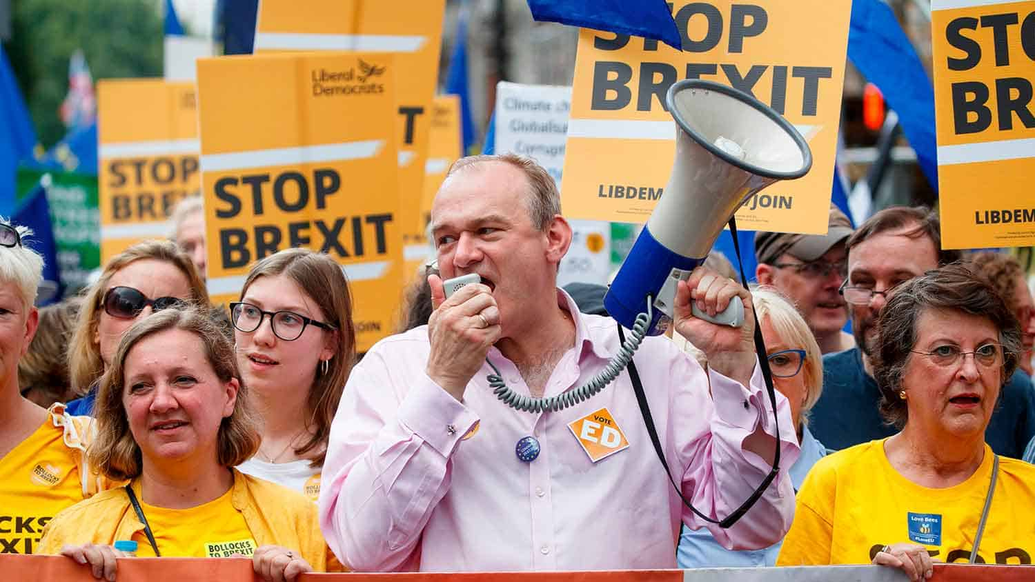 Sir Ed Davey MP addressing a crowd with a megaphone, in the background supporters are dressed in yellow