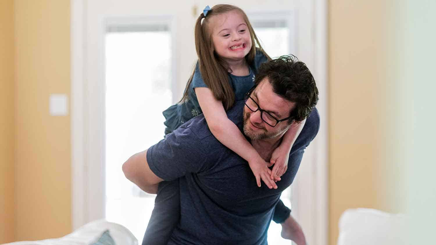 A young girl with Down Syndrome is given a piggy back by a man, both are laughing.