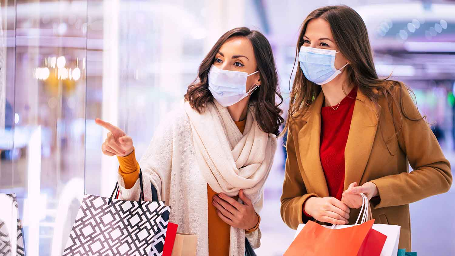 Two women out shopping both wearing PPE masks