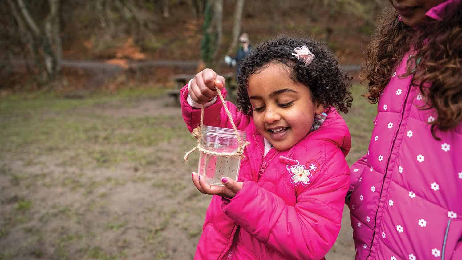 young girl marvelling at something she's caught in a glass beaker in a park.