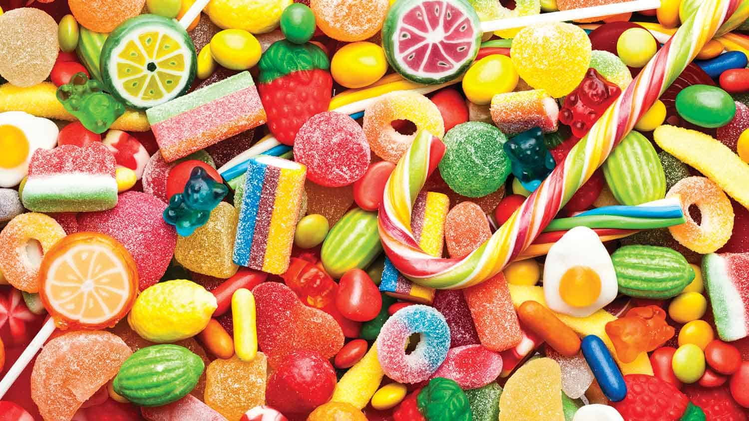 A variety of brightly coloured sugary sweets spread out on a table