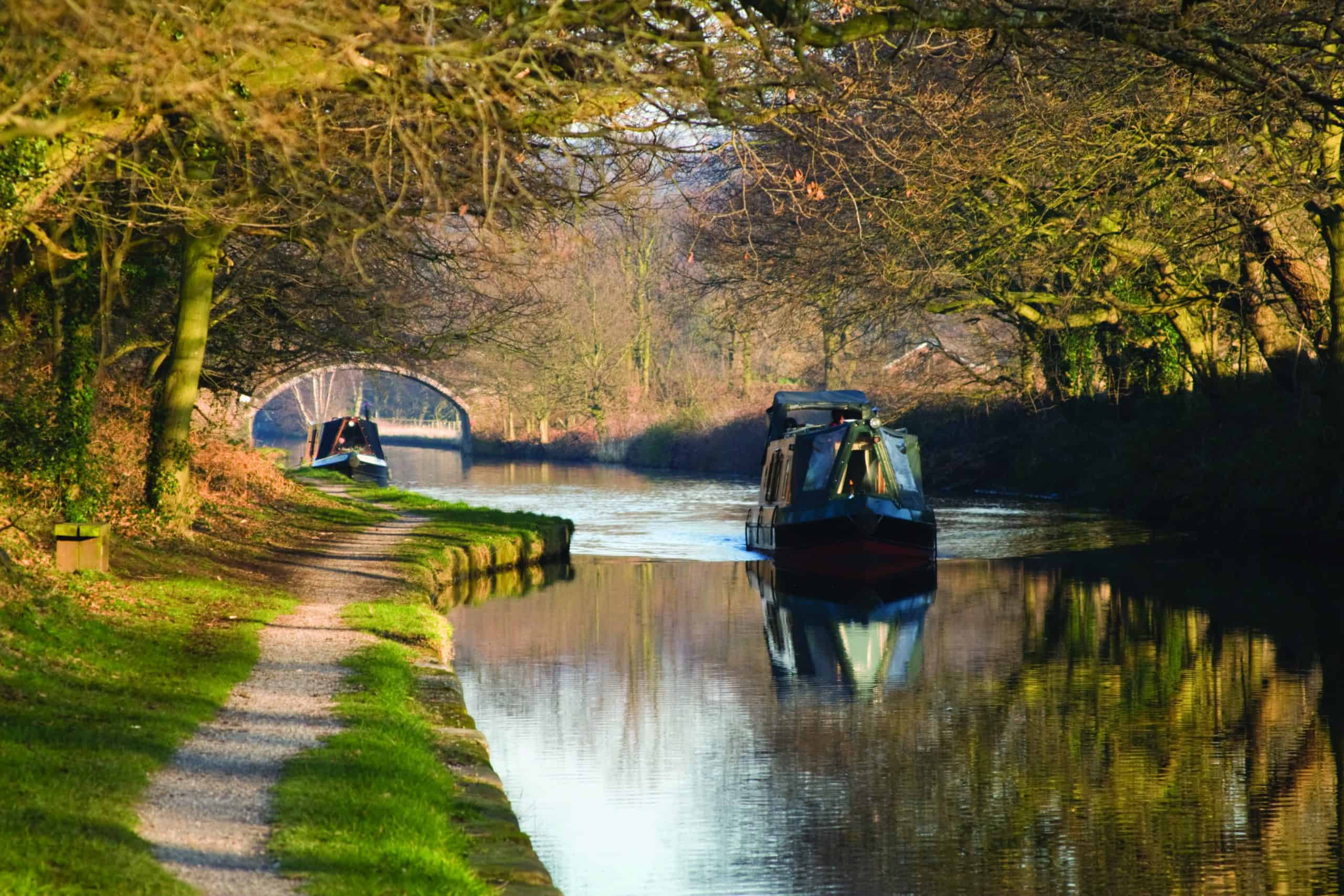 A canal with canal boats floating on it